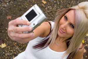 A young woman taking pictures of herself with a digital camera.