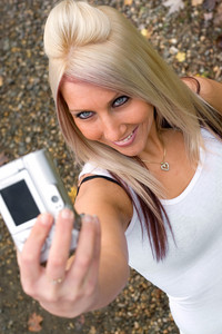 A young woman taking pictures of themselves with a digital camera.