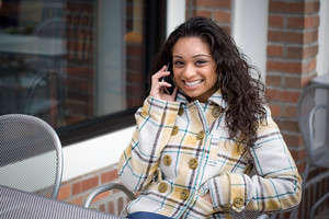 A young woman talking on her cell phone outdoors while seated at a cafe table.
