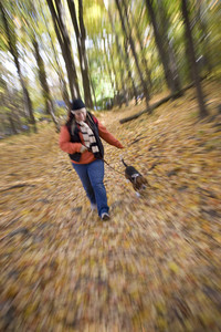 A young woman walking her dog through the woods with a zoom blur effect.