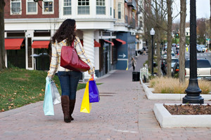 A young woman walking in the city doing some shopping.