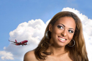 A young woman with a big smile on her face thinking about traveling or taking a vacation to an exotic place.