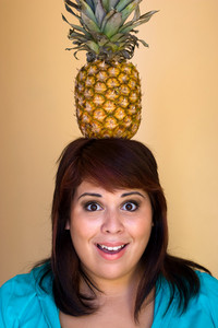 A young woman with a funny expression balancing a pineapple on her head.