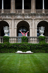 A young woman with her arms up in the air in front of a fancy mansion.