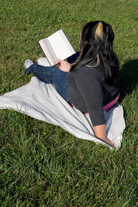A young woman with highlighted hair reading a book on the school campus.