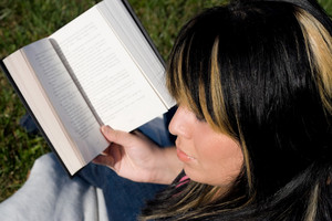 A young woman with highlighted hair reading a book or doing homework on campus.  Shallow depth of field.