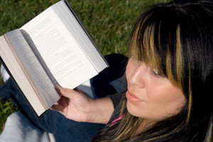 A young woman with highlighted hair reading a book or doing homework on campus.