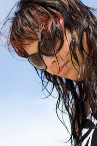 A young woman with wet hair at the beach.  Shallow depth of field.