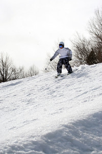 A youth freestyle skier skiing down the snowy mountain.