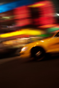 Abstract blur of a city street scene at night with a yellow taxi cab speeding by.  Slow shutter speed panning technique used for motion blur.