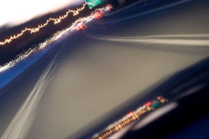 Abstract blur of a drivers view at high speed on an urban road or highway around dusk. Intentional motion blur.