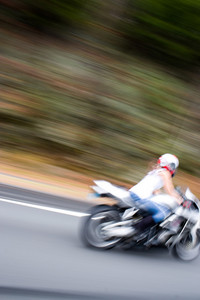Abstract blur of a pretty girl driving a motorcycle at highway speeds.  Intentional motion blur.
