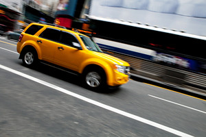 Abstract blur of a speeding taxi SUV truck in New York City.  Slow shutter speed panning technique used for intentional motion blur.