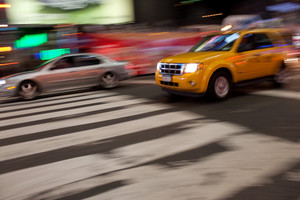 Abstract blur of a street scene in New York City with a yellow taxi cab speeding by.  Slow shutter speed panning technique used for motion blur.