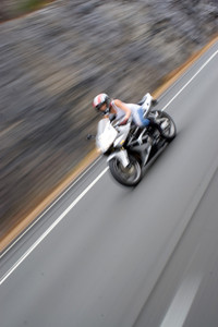 Abstract blur of a woman driving a motorcycle at highway speeds.  Intentional motion blur.