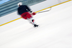Abstract motion blur of a hockey player as he skates down the ice. Slight motion blur and shallow depth of field.