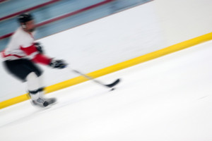 Abstract motion blur of a hockey player handling the puck as he speeds down the ice.