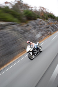 Abstract motion blur of a woman driving a fast motorcycle at highway speeds.