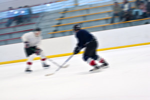Abstract motion blur of two hockey players skating down the ice rink.