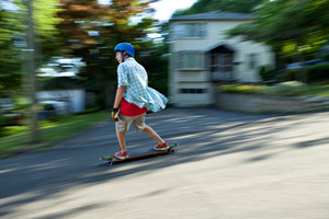 Action shot of a longboarder skating on an urban road. Slight motion blur from panning technique to capture movement.