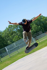 Action shot of a skateboarder doing tricks on his skateboard at the skate park.
