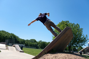 Action shot of a skateboarder going up a concrete skateboarding ramp at the skate park.
