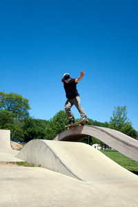 Action shot of a skateboarder performing a grind at a concrete skate park.
