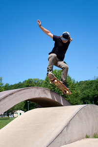 Action shot of a skateboarder performing a jump at a skate park.