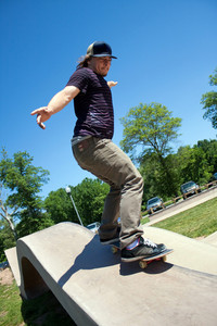 Action shot of a skateboarder performing a rail grind at a skate park.