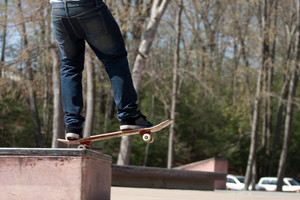 Action shot of a skateboarder skating at the park on a concrete rail.