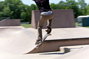 Action shot of a skateboarder skating at the skate park with concrete ramps. Slight motion blur.