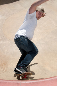 Action shot of a skateboarder skating in a concrete skateboarding bowl at the skate park.