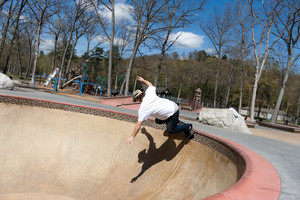 Action shot of a young skateboarder skating sideways against the wall of the bowl at a skate park.