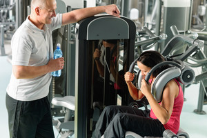 Active man and woman at fitness center exercise abdominal machine