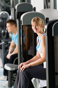Active woman and man at fitness center exercise on machine