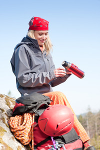 Active young woman rock climbing relax with thermosbottle on mountain
