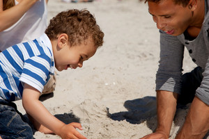 Adorable kid enjoys as he plays in the sand with his dad