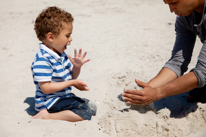 Adorable kid looking excited as his dad makes a sand castle on a beach