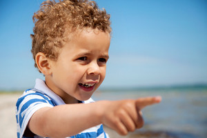 Adorable little kid pointing at something interesting outdoors