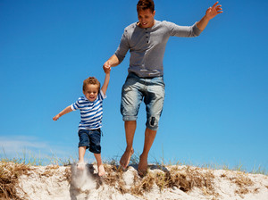 Adorable portrait of a young dad and his son jumping outdoors