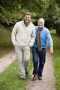 Adult father and aon walking along woodland path in autumn
