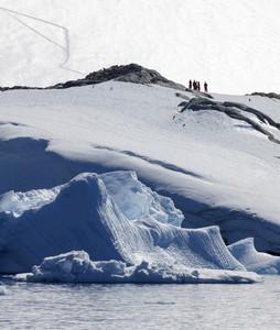 Adventurers atop a snowy cliff along the coast