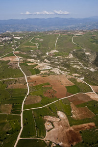 Aerial View At Farm Fields In Front Of Misty Mountains