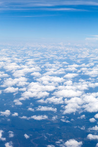 Aerial view of the blue skies and horizon with fluffy clouds and the earth below.