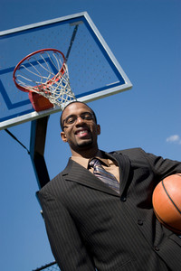 African American man in a business suit posing with a basketball.  He could be a coach player recruiter or trainer.