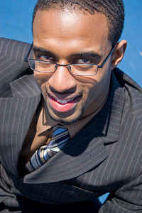 African American man in a business suit with eye glasses smiling happily.