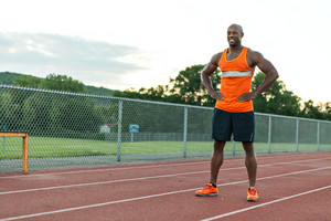 African American man in his 30s posing at a sports track outdoors.