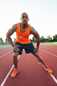 African American man in his 30s stretching at a sports track outdoors.