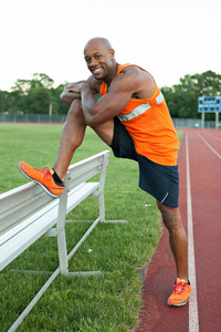 African American man in his 30s stretching out before a run at a sports track outdoors.