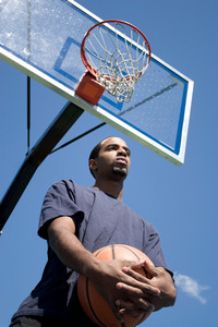 African American man posing with a basketball beneath the backboard.